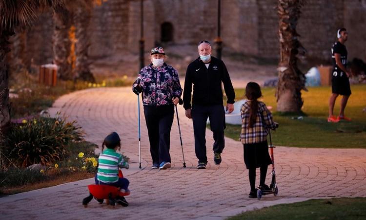 Người dân đeo khẩu trang đi bộ thể dục trong một công viên ở Ashkelon, Israel, hồi tháng 5. Ảnh: Reuters.