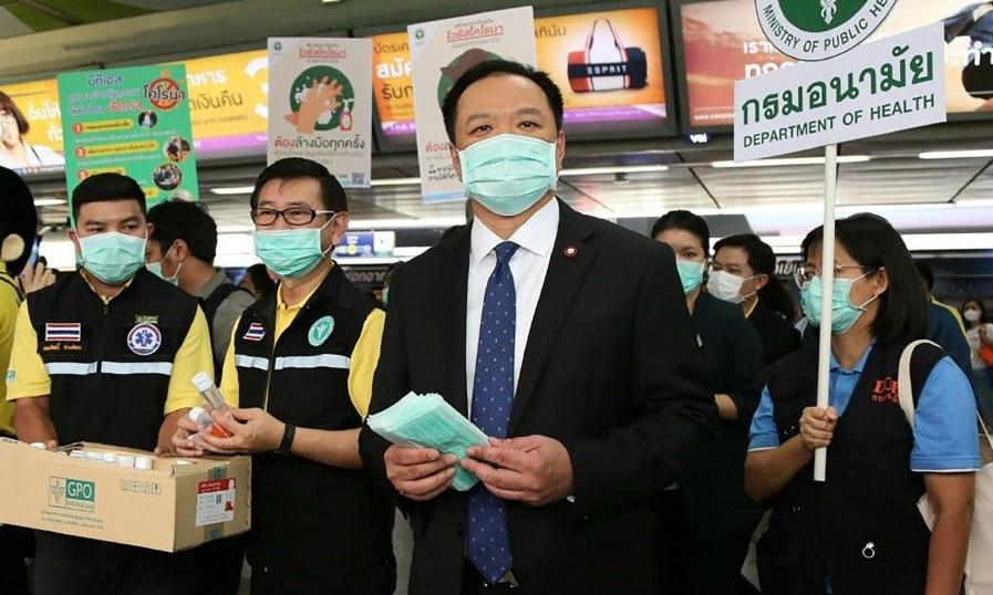 Bộ trưởng Charnvirakul (giữa) phát khẩu trang tại một ga tàu điện ở Bangkok hồi tháng 2. Ảnh: AFP.