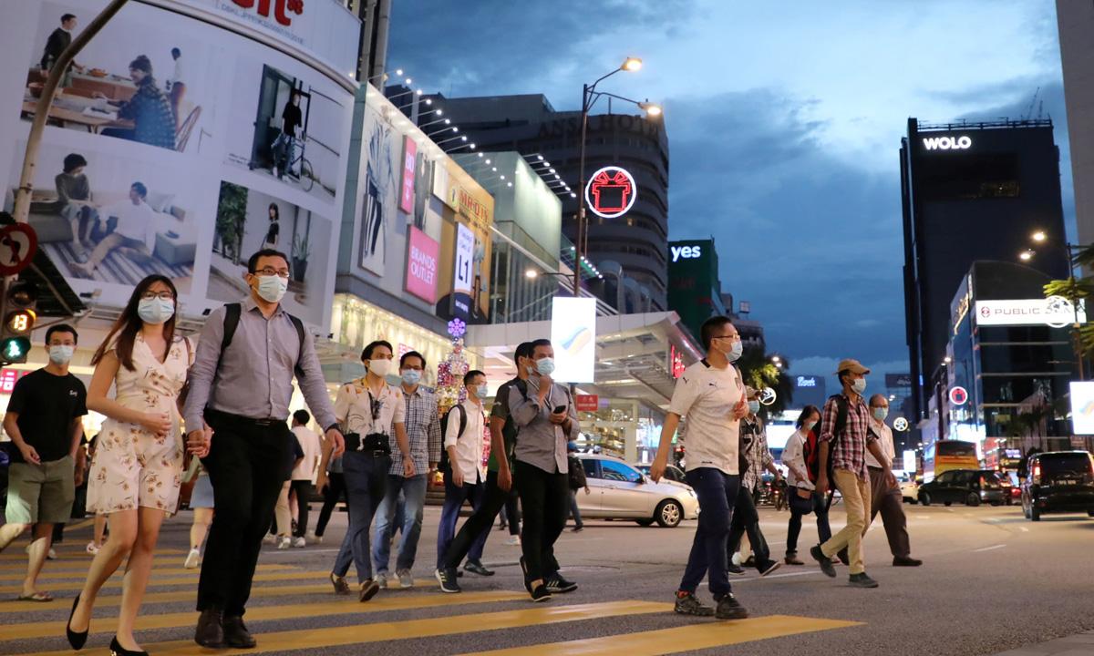 Người dân đeo khẩu trang trên một con phố ở Kuala Lumpur, Malaysia, hôm 17/12. Ảnh: Reuters.