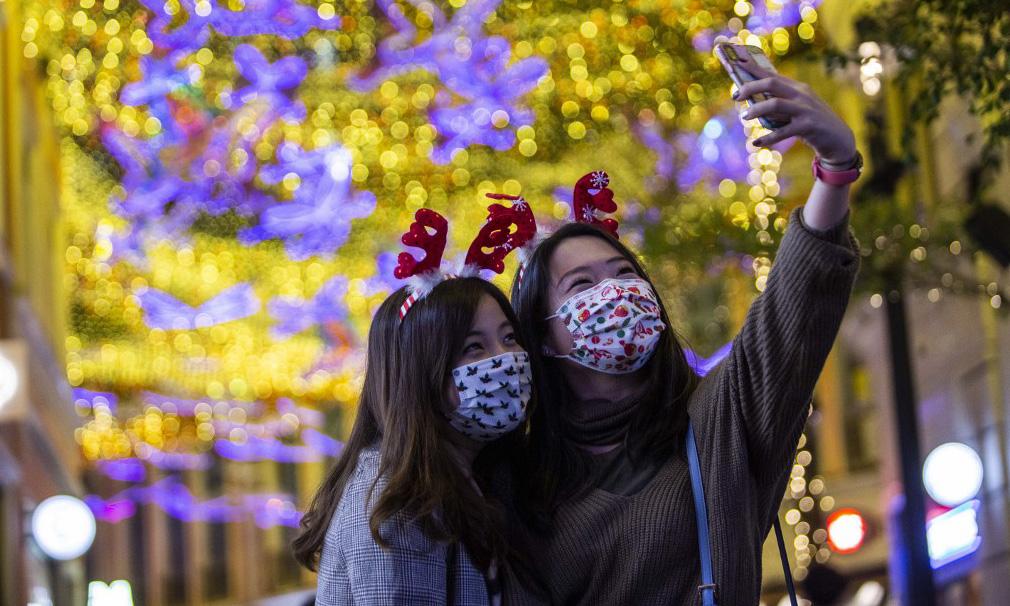 Người dân Hong Kong đeo khẩu trang đón Giáng sinh tại một trung tâm thương mại hôm 24/12. Ảnh: AFP.