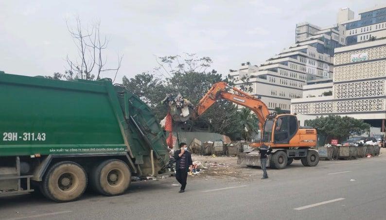 Xe cuốn ép và máy xúc được huy động thu gom rác tồn đọng trên địa bàn quận Nam Từ Liêm, chiều 30/12. Ảnh: Tất Định