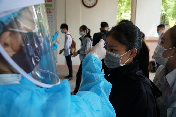 Học sinh trường THPT Trần Quốc Tuấn, TP Quảng Ngãi, đo thân nhiệt trước khi làm thủ tục dự thi tốt nghiệp THPT hồi tháng 8. Ảnh:Phạm Linh.