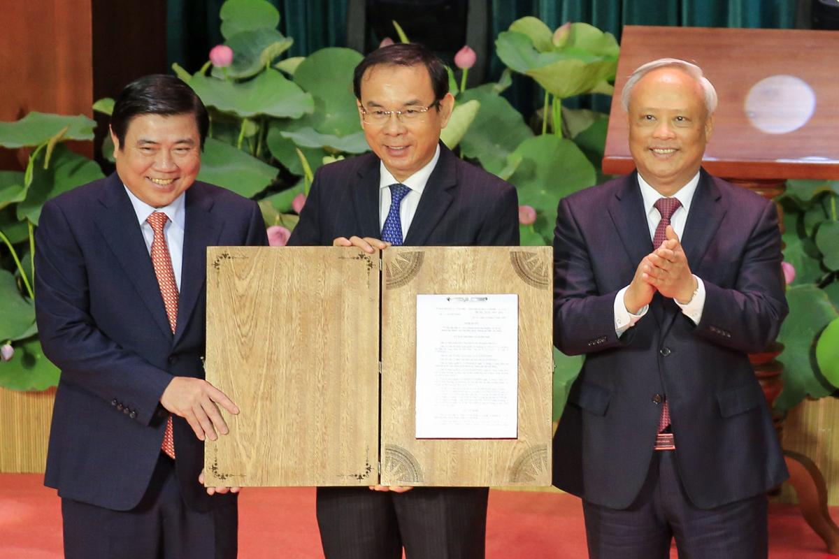 Phó chủ tịch Quốc hội Uông Chu Lưu (phải) trao Nghị quyết cho lãnh đạo Thành uỷ, UBND TP HCM. Ảnh: Hữu Công.