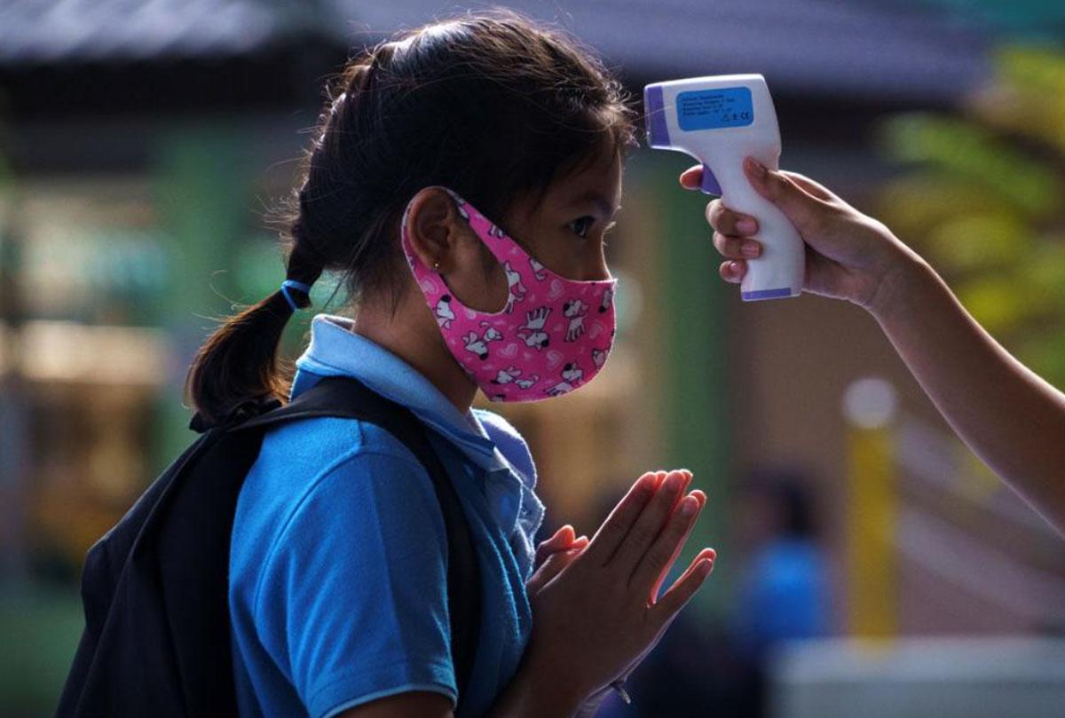 Học sinh tại thủ đô Bangkok đeo khẩu trang, kiểm tra thân nhiệt trước khi vào trường ngày 7/10/2020. Ảnh: Athit Perawongmetha/ Reuters.