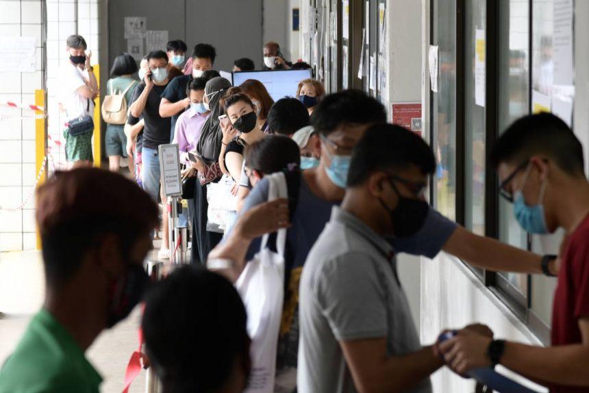 Đám đông phụ huynh xếp hàng trước cửa hàng bán đồng phục, không tuân thủ quy định giãn cách, ngày 29/12/2020. Ảnh: Straits Times