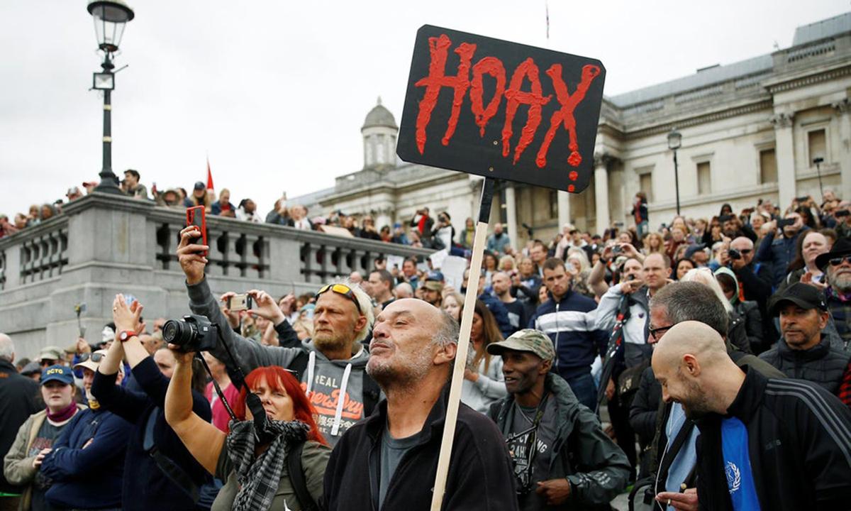 Một người biểu tình mang tấm biển với dòng chữ đỏ Hoax (Trò lừa bịp) khi biểu tình chống phong tỏa và đeo khẩu trang ở quảng trường Trafalgar, London. Ảnh: Reuters.