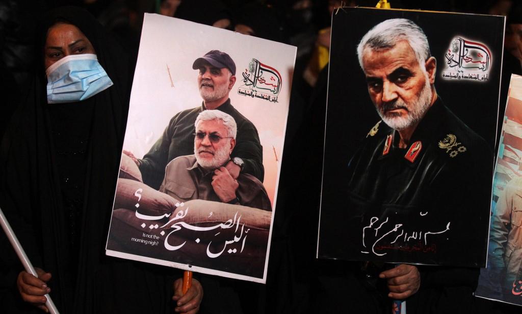 Người dân hôm 2/1 cầm ảnh tướng Qassem Soleimani (phải) và Abu Mahdi al-Muhandis, cố chỉ huy một nhóm dân quân Iraq thân Iran, tại sân bay Baghdad, Iraq, nơi hai người bị ám sát một năm trước. Ảnh: AFP.