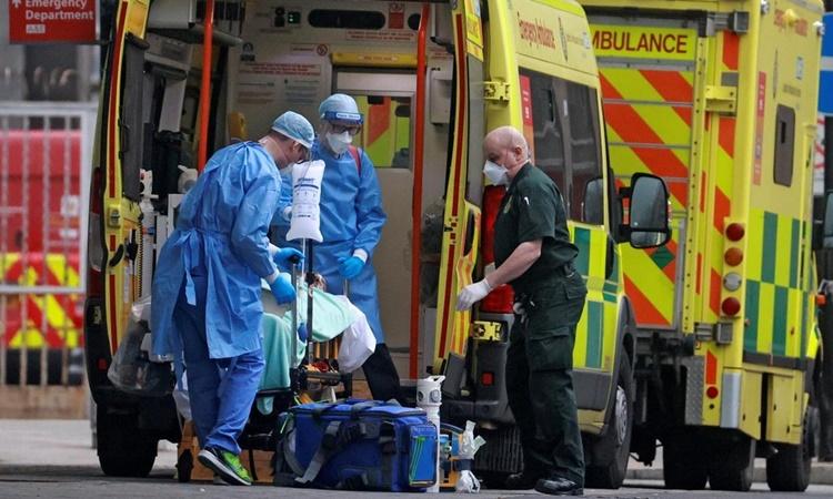 Nhân viên y tế di chuyển một bệnh nhân nghi nhiễm Covid-19 tại London, Anh, hồi tháng trước. Ảnh: Reuters.