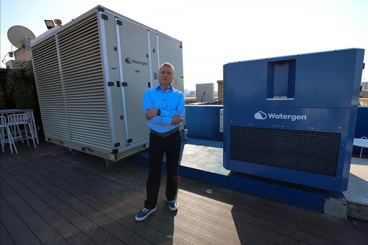 CEO Watergen Michael Mirilashvili đứng cạnh một cỗ máy chiết xuất nước từ không khí. Ảnh: AFP.