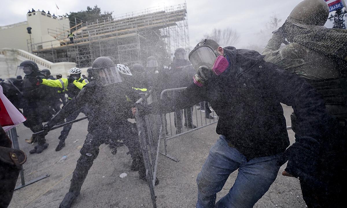 Cảnh sát chống bạo động dùng dùi cui và hơi cay đẩy lùi người biểu tình đang cố phá vỡ hàng rào an ninh bên ngoài Quốc hội Mỹ, ngày 6/1. Ảnh: WP.