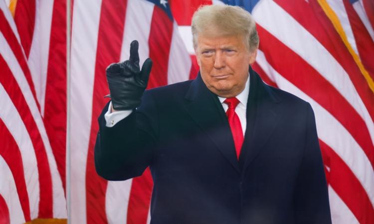 Tổng thống Mỹ Trump đứng sau tấm kính chống đạn trong cuộc mít tinh ở Washington ngày 6/1. Ảnh: Reuters.