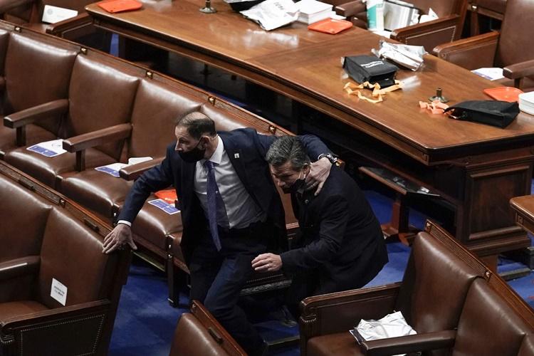 Các nghị sĩ trong phòng họp Hạ viện cúi đầu tìm nơi ẩn nấp khi những người ủng hộ Tổng thống Trump tràn vào tòa nhà quốc hội. Ảnh: AP.