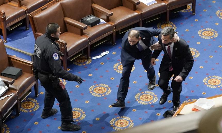 Các nghị sĩ tìm nơi trú ẩn khi người biểu tình xông vào Điện Capitol hôm 6/1. Ảnh: AFP.