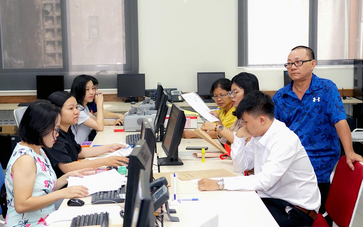 Cán bộ tuyển sinh Đại học Hoa sen làm thủ tục xét tuyển cho thí sinh. Ảnh: Lê Nam.