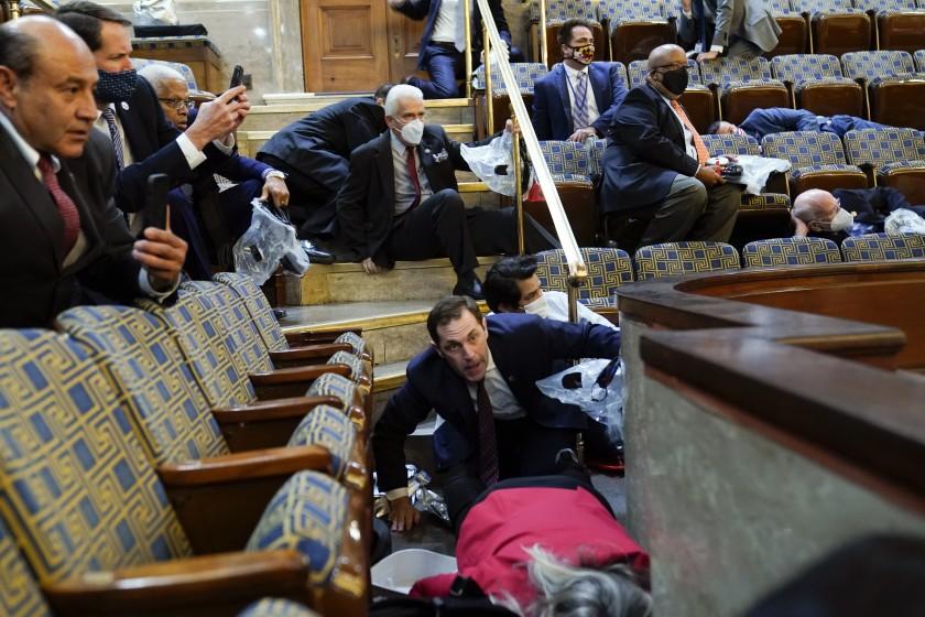 Các nghị sĩ núp xuống ghế khi người ủng hộ Trump xông vào Điện Capitol ngày 6/1. Ảnh: AP.