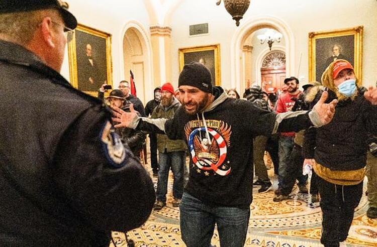 Người ủng hộ Trump chạm trán cảnh sát trong tòa quốc hội ngày 6/1. Ảnh: AP.