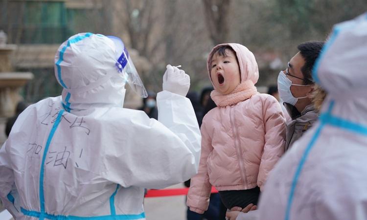 Nhân viên y tế lấy mẫu xét nghiệm Covid-19 cho người dân ở Thạch Gia Trang, tỉnh Hà Bắc, Trung Quốc hôm 6/1. Ảnh: Xinhua.