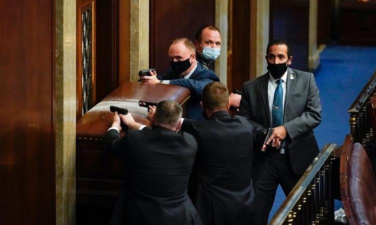 Nhân viên an ninh chĩa súng về một trong những cánh cửa của phòng họp Hạ viện Mỹ để cảnh giới khi những người biểu tình gây náo loạn ở bên ngoài. Ảnh: AP.