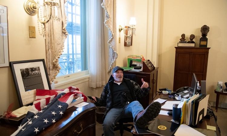 Richard Barnett gác chân lên bàn làm việc của Chủ tịch Hạ viện Mỹ Pelosi hôm 6/1. Ảnh: AFP.