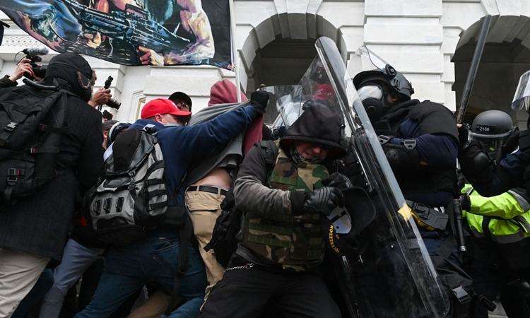 Người ủng hộ Tổng thống Trump đụng độ với cảnh sát bên ngoài tòa nhà quốc hội Mỹ hôm 6/1. Ảnh: AFP.