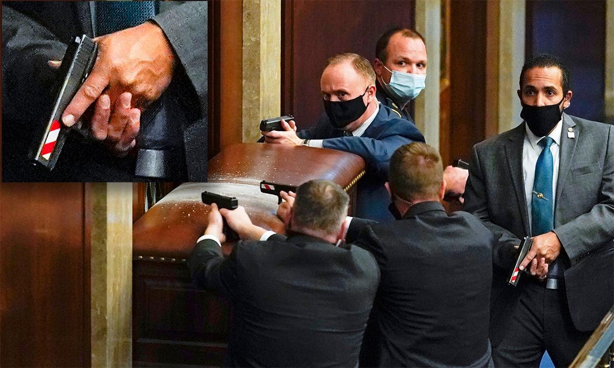 Cảnh sát quốc hội Mỹ mặc thường phục cầm súng ngắn dán băng phản quan sọc trắng đỏ răn đe người biểu tình quá khích, ngày 6/1. Ảnh: AP.