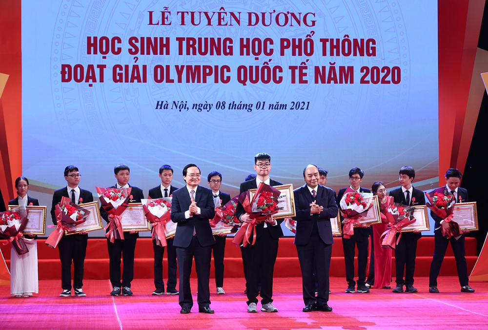 Thủ tướng Nguyễn Xuân Phúc và Bộ trưởng Giáo dục và Đào tạo Phùng Xuân Nhạ trao huân chương lao động, hoa chúc mừng cho các học sinh. Ảnh: MOET.
