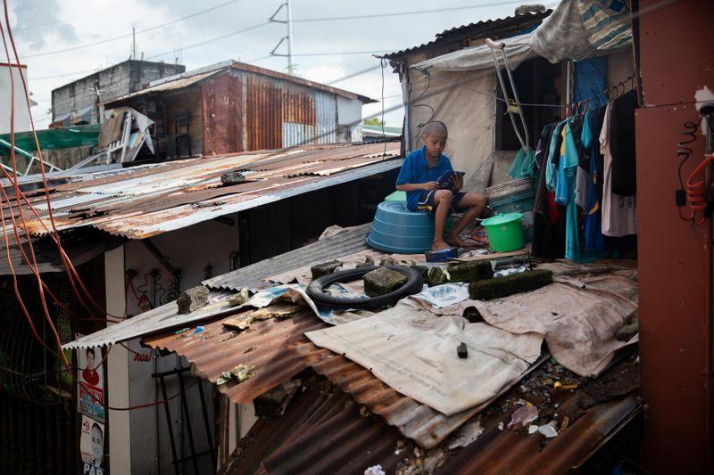 Jhay Ar Calma ngồi trên mái tôn để thu tín hiệu Internet. Ảnh: Eloisa Lopez/ Reuters