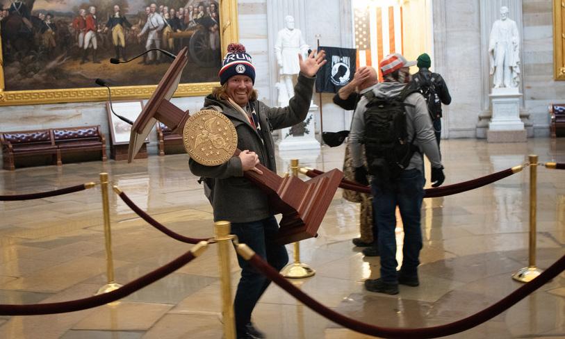 Người đàn ông ôm bục phát biểu của Hạ viện rời tòa nhà quốc hội Mỹ ở Washington hôm 6/1. Ảnh: Win McNamee.