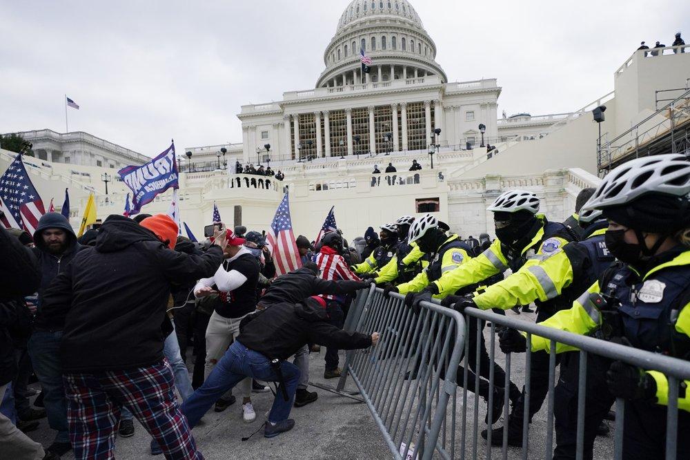 Người ủng hộ Trump cố kéo đổ hàng rào an ninh của cảnh sát trước tòa quốc hội hôm 6/1. Ảnh: AP.