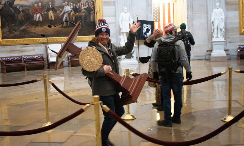 Người đàn ông ôm bục phát biểu của Chủ tịch Hạ viện rời tòa nhà quốc hội Mỹ ở Washington hôm 6/1. Ảnh:Win McNamee.