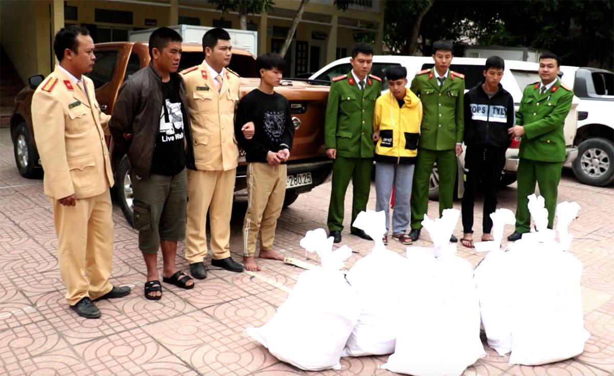 8 bao tải chứa ma túy và nhóm nghi phạm lúc cảnh sát dẫn giải về trụ sở. Ảnh: Phương Linh