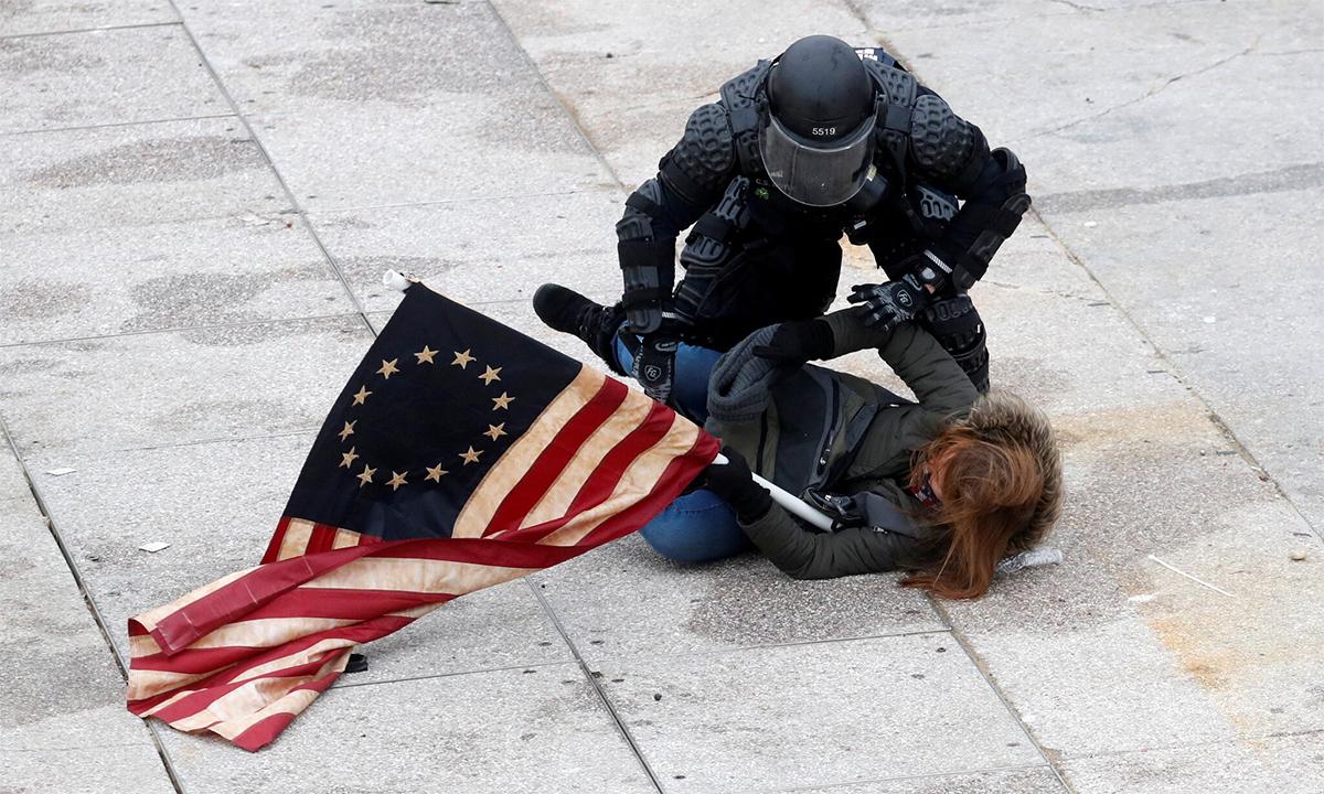 Cảnh sát quốc hội Mỹ vật ngã một người biểu tình quá khích mang theo cơ Liên minh miền Nam, ngày 6/1. Ảnh: Reuters.