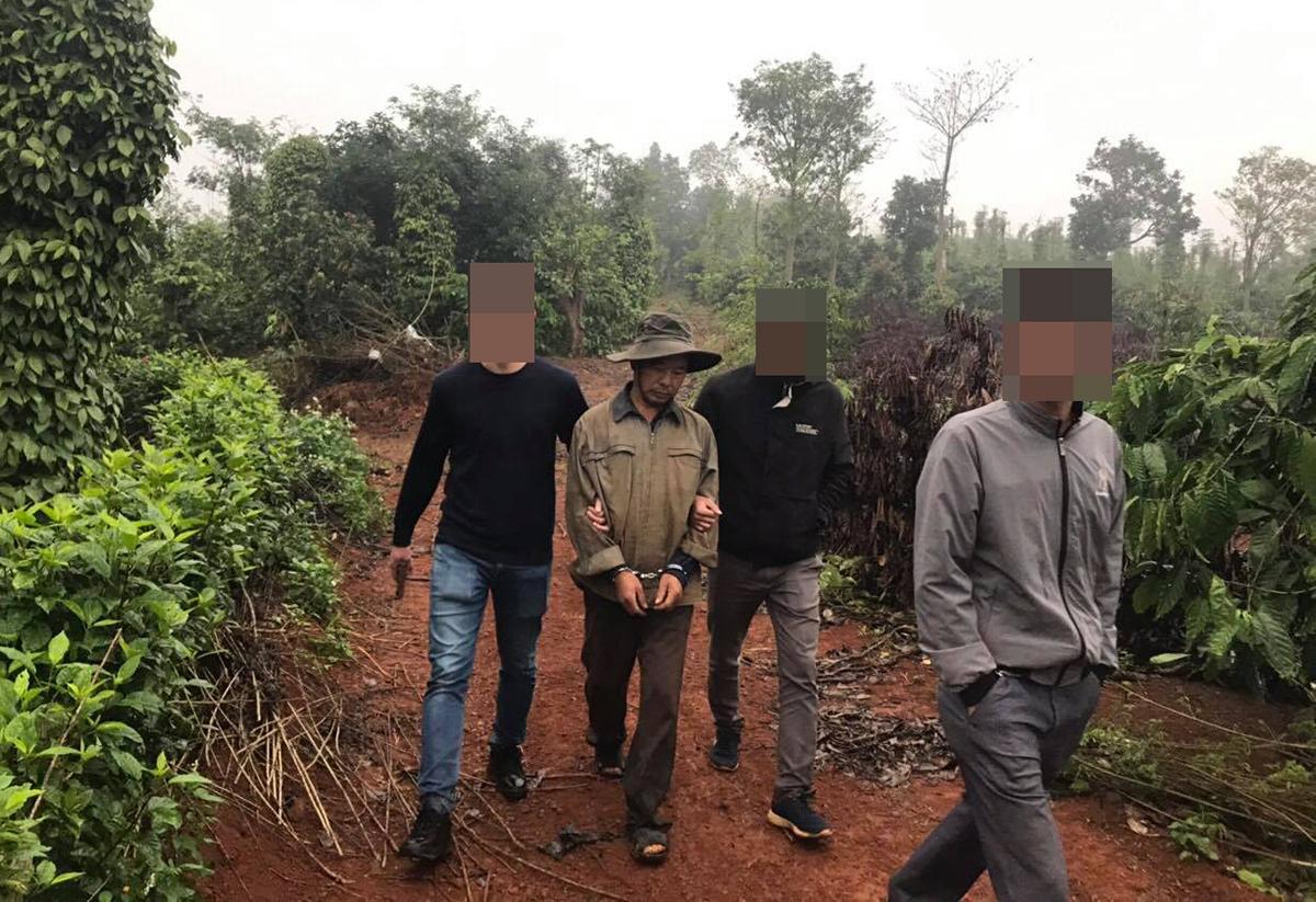 Cảnh sát áp giải Vỵ trong rừng ra ngoài. Ảnh: Công an cung cấp.