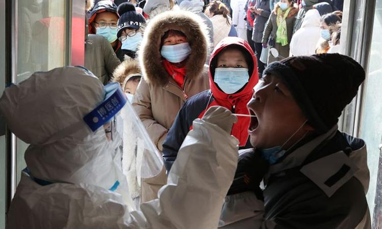 Nhân viên y tế lấy mẫu xét nghiệm Covid-19 cho người dân thành phố Thạch Gia Trang, tỉnh Hà Bắc hôm 6/1. Ảnh: Reuters.
