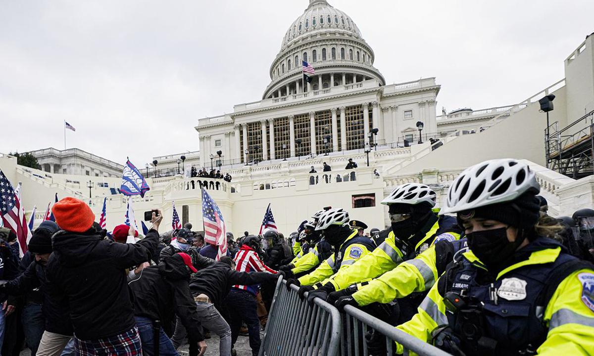 Người biểu tình ủng hộ Trump cố gắng phá hàng rào bảo vệ của cảnh sát trước tòa nhà quốc hội Mỹ hôm 6/1. Ảnh: AP.