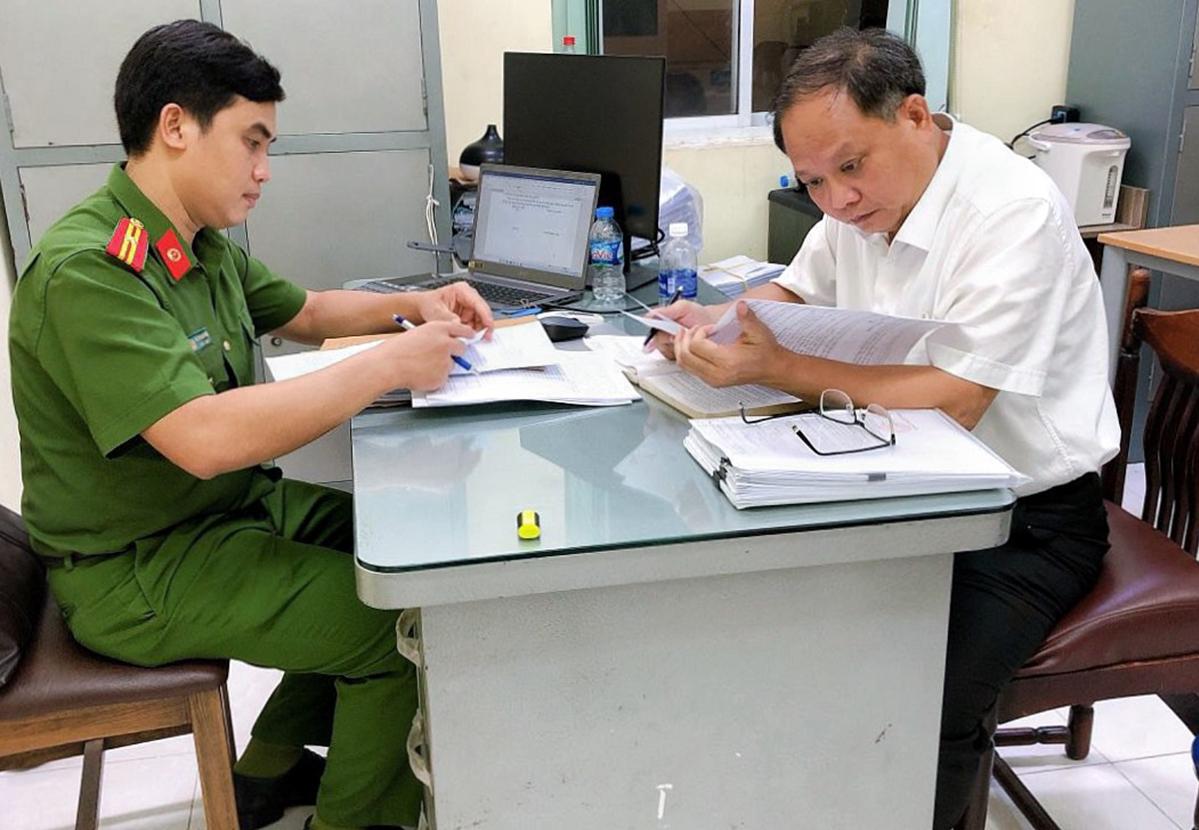 Ông Tất Thành Cang (phải) sau khi nhận quyết định khởi tố bị can, bắt tạm giam, chiều 16/12. Ảnh:Công an cung cấp.