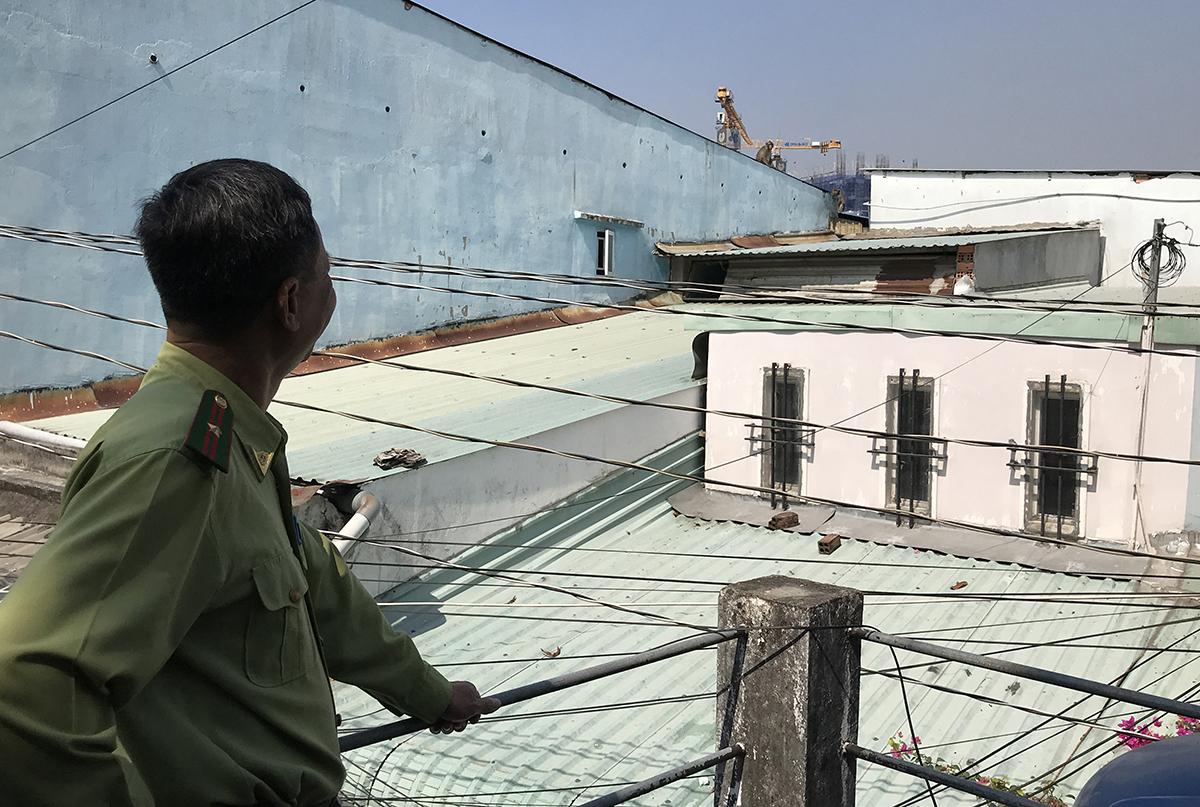 Nhân viên kiểm lâm TP HCM quan sát đàn khỉ đang trèo trên mái tôn. Ảnh: Đình Văn.