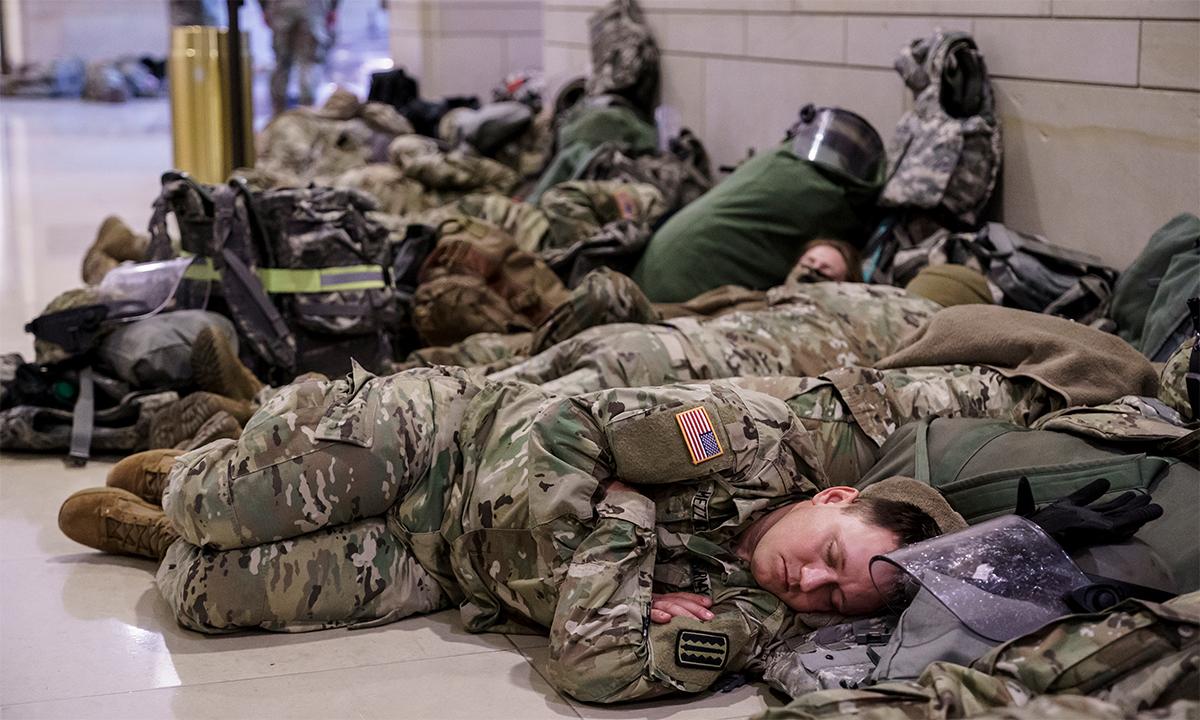 Vệ binh quốc gia nằm ngủ trong giờ nghỉ giữa ca tại tòa nhà quốc hội Mỹ, ngày 13/1. Ảnh: AP.