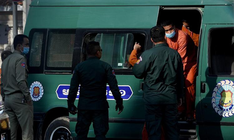 Các chính trị gia và nhà hoạt động đối lập được đưa ra khỏi xe nhà tù trước một tòa án tại thủ đô Phnom Penh, Campuchia hôm nay. Ảnh: AFP.