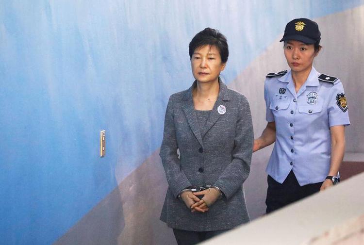 Cựu tổng thống Hàn Quốc Park Geun-hye (trái) được áp giải đến phiên tòa ở Seol năm 2017. Ảnh: Reuters.