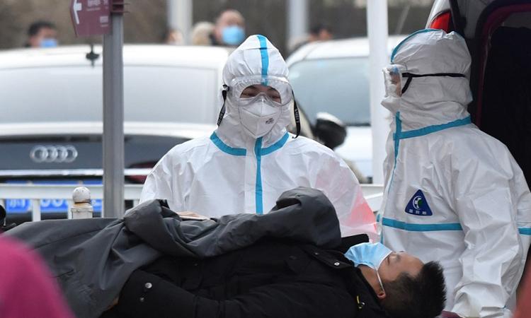 Nhân viên y tế mặc đồ bảo hộ phòng Covid-19 khi di chuyển bệnh nhân có biểu hiện sốt đến một bệnh viện ở Bắc Kinh, Trung Quốc hôm 13/1. Ảnh: AFP.