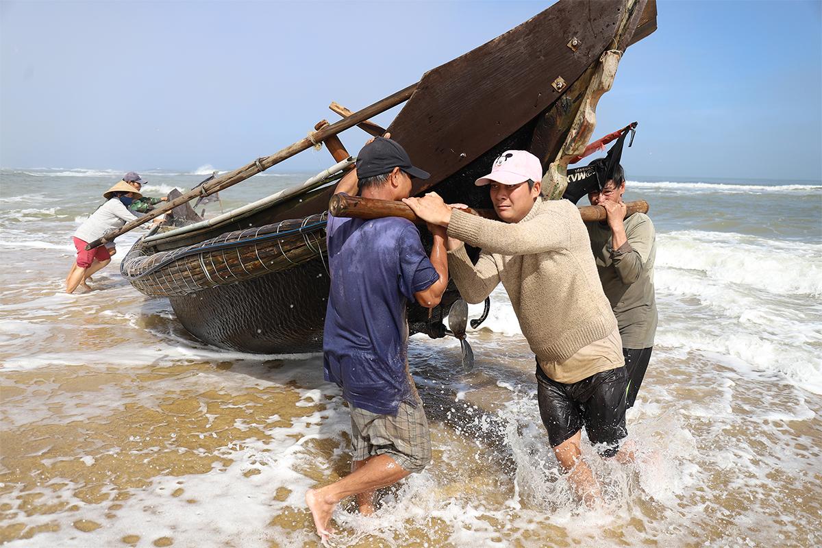 Ông Sáu và hai bạn thuyền gánh thuyền đưa lên bờ cát. Ảnh: Võ Thạnh