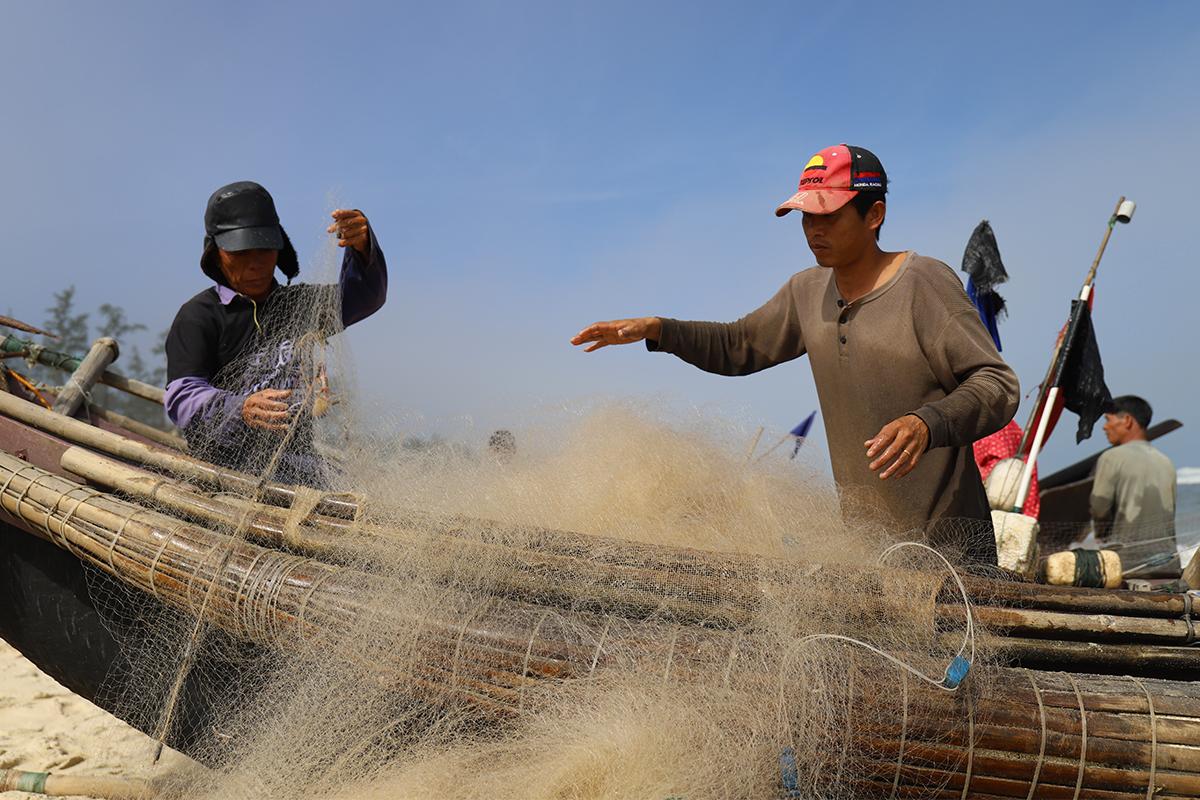 Người dân gỡ cá khoai khỏi lưới sau khi thuyền cập bờ. Ảnh: Võ Thạnh