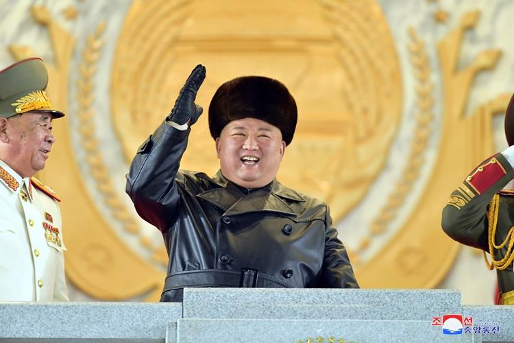 Lãnh đạo Triều Tiên Kim Jong-un tươi cười vẫy tay khi giám sát cuộc duyệt binh đêm 14/1. Ảnh: KCNA.