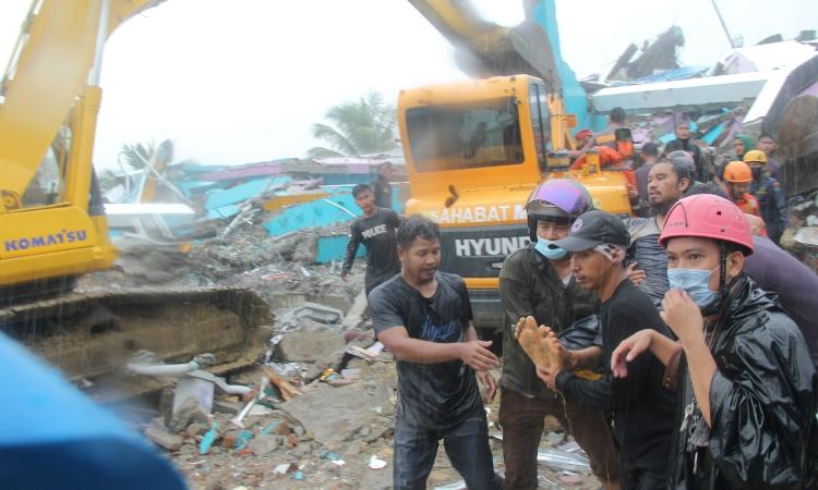 Người dân cùng lực lượng cứu hộ vận chuyển một nạn nhân còn sống dưới đống đổ nát ở thành phố Mamuju, tỉnh Tây Sulawesi, Indonesia, hôm 15/1. Ảnh: Reuters.