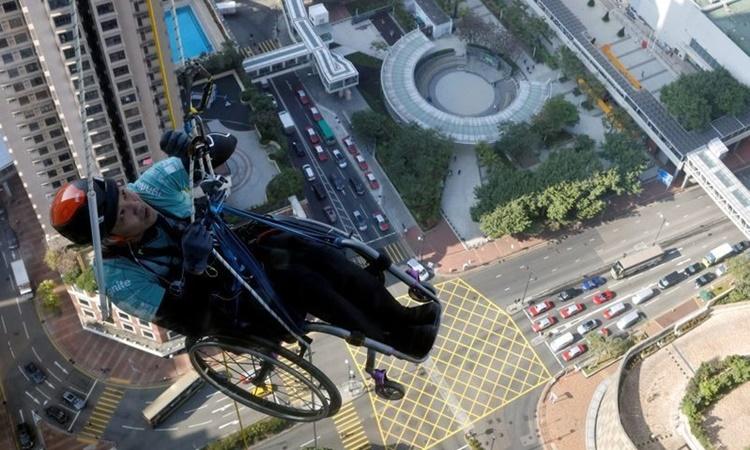 Lai Chi-wai leo lên tòa nhà Nina Town ở bán đảo Cửu Long, Hong Kong, trên xe lăn ngày 17/1. Ảnh: Reuters.