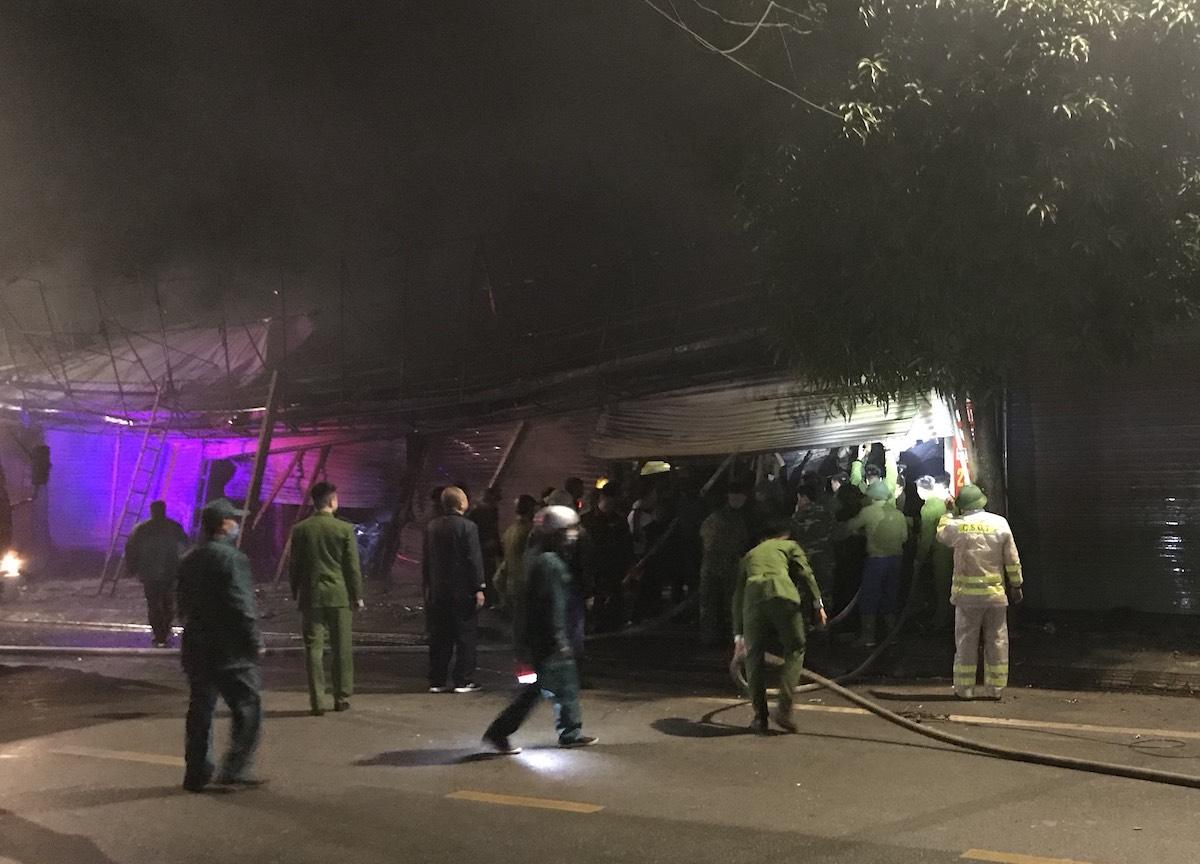 Cảnh sát tiết cận cửa hàng dập lửa. Ảnh: Quang Trung