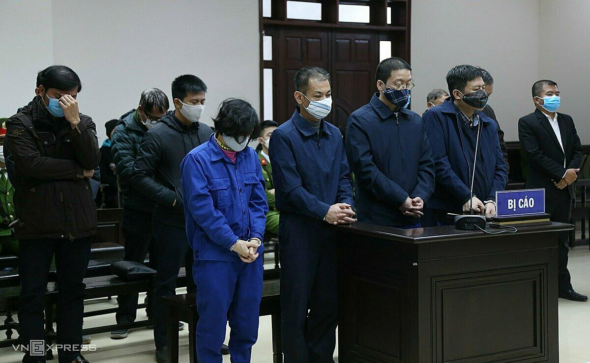 Bị cáo Hoa Hữu Long (hàng đầu, thứ hai từ trái) cùng 13 đồng phạm tại phiên xét xử. Ảnh: Phạm Dự