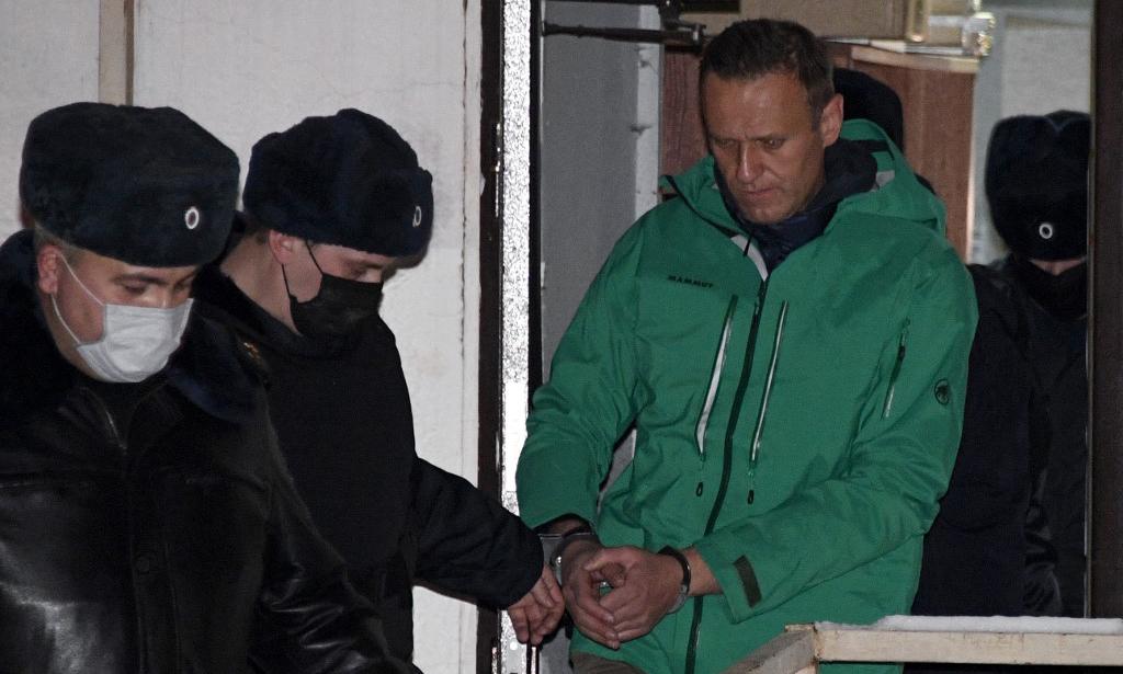 Alexei Navalny (áo xanh) bị áp giải ra khỏi một đồn cảnh sát ở ngoại ô Moskva, Nga, hôm 18/1. Ảnh: AFP.