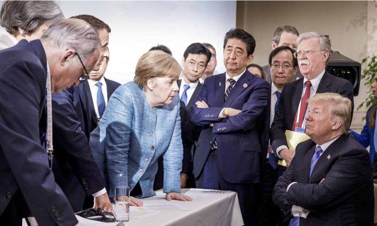 Tổng thống Mỹ ngồi khoanh tay, trước mặt ông là Thủ tướng Đức Angela Merkel và các lãnh đạo G7 khác trong cuộc họp G7 tại Canada tháng 6/2018. Ảnh: AP.